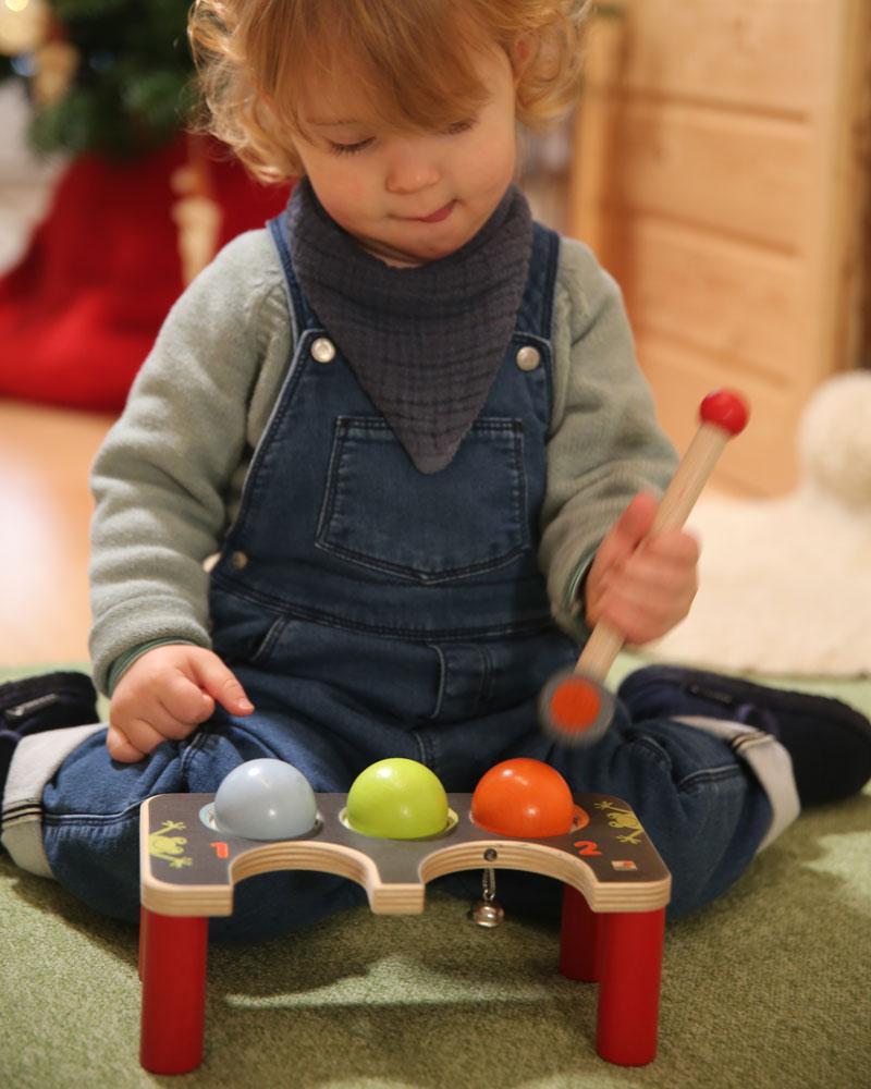 Enfant avec des jouets en bois de croquet de percussion de Selecta