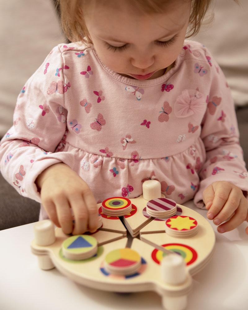 Enfant avec le poussoir jouets en bois colorés de Selecta