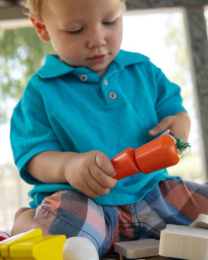 Un enfant avec des jouets de Pique-nique en bois par Selecta